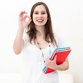 smiling woman hand gesture ok sign and holding notepad, isolated over white
