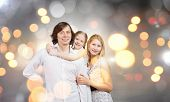 Happy family of mother father and daughter against bokeh background