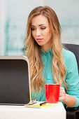 Young blond woman working with a laptop
