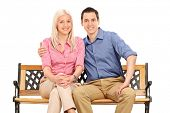 Cheerful young couple posing seated on a bench isolated on white background