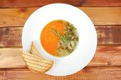 european cuisine: vegetable soup with toasts on white dish over wooden table