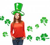 gestures, holidays, st. patricks day and people concept - happy teenager in green top hat over white background with shamrock or clover