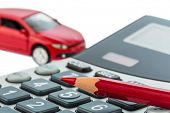 stock photo of calculator  - a car and a red pen lying on a calculator - JPG