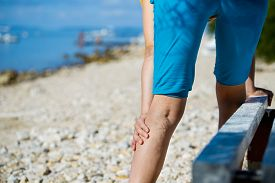image of varicose  - Woman touching painful varicose veins on a leg - JPG