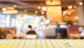 stock photo of mature adult  - Empty wood table and blurred coffee shop background  - JPG
