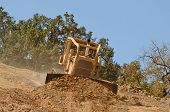 image of bulldozers  - Large bulldozer moving rock and soil for fill for a new commercial development road construction project - JPG