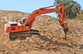 stock photo of claw  - Large track hoe excavator using a claw ripper to break up rock and soil for fill for a new commercial development road construction project - JPG
