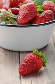 stock photo of strawberry  - strawberry closeup on the foreground on the background of a full bowl of strawberries - JPG