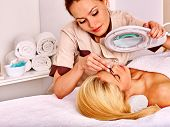 picture of eyebrows  - Woman getting tweezing eyebrow by beautician - JPG