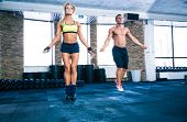 stock photo of skipping rope  - Handsome muscular man and beautiful sporty woman workout with jumping rope in gym - JPG