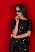 stock photo of little black dress  - Beautiful brunette girl in a black dress and glasses - JPG