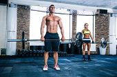 picture of gym workout  - Muscular man and woman workout with barbell at gym - JPG