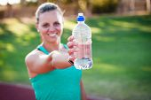 stock photo of bottles  - female athlete holding a bottle of water in front of her with the focus on the water bottle - JPG