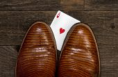 stock photo of cheating  - Poker player with cheating hand under cowboy boot - JPG