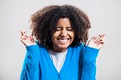 pic of fingers crossed  - Studio portrait of african ethnicity woman with crossed fingers - JPG