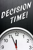 stock photo of midnight  - The phrase Decision Time in white text on a blackboard above a modern clock face with the time at almost midnight or twelve noon - JPG