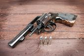 pic of revolver  - black revolver gun with bullets isolated on wooden background - JPG