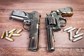 image of guns  - Black revolver gun and Semi-automatic 9mm gun on wooden background.