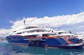 stock photo of ski boat  - luxury Mega super yachts docked in harbour with jet ski inside - JPG