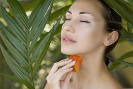 stock photo of papaya fruit  - Beautiful caucasian woman having fresh papaya natural facial mask apply skin care and wellness - JPG