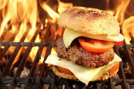 stock photo of burger  - Homemade BBQ Beef Burger On The Hot Flaming Grill. Good Snack For Outdoors Summer Party Or Picnic ** Note: Shallow depth of field - JPG