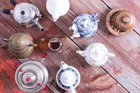 picture of brew  - Easy tea from a teabag versus quality brewed tea from a tea pot in a conceptual image with a central cup of tea surrounded by a circle of different teapots on a rustic wooden table viewed from above - JPG
