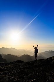 stock photo of climb up  - Woman successful hiking climbing silhouette in mountains motivation and inspiration in beautiful sunset and ocean - JPG