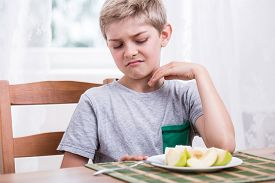 image of fussy  - Blonde boy refusing to eat healthy apple - JPG