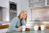 Young blond woman drinking coffee in her kitchen