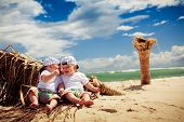 identical twin boys relaxing on tropical beach