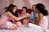 stock photo of slumber party  - Five friends enjoying popcorn together at a slumber party - JPG