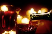 Pouring red wine in candle-light (Shallow DOF - focus on wine pouring)