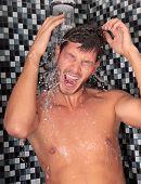 Hombre que tiene ducha en el baño con jabón y champú