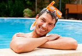 Smiling swimming-pool man laughing and smiling while having summer holiday vacations in a resort