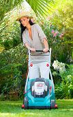 Home garden grass cutting woman mowing with lawn mower in tropical green