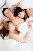 Successful man lying with two girls in bed