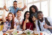 eating, food and people concept - group of happy international friends showing thumbs up gesture at  poster