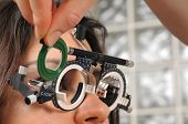 Beautiful young female patient having a medical examination at optician - a series of eye exam relat