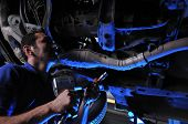 Auto mechanic working under dramatically lightened car - a series of MECHANIC related images.