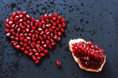 Pomegranate Seeds Are Stacked In The Form Of A Heart On A Black Background, Sprinkled With Water, Ne poster