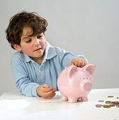 muchacho insertar una moneda en una alcancía