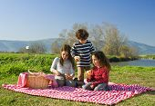 Drei Kinder essen Brötchen bei einem Picknick