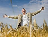 businessman with spread out arms in a rye field