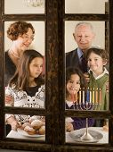 grandparents and grandchildren with Hanukkia, at the window