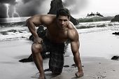 Dark stylized portrait of a young muscular shirtless man on the beach with storm and crashing waves