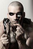 Постер, плакат: Портрет стилизованными моды экстрима глядя мужской модели с бритые головы и глаз макияж держа нож