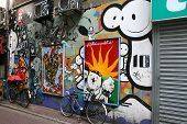 City graffity in Amsterdam. Holland. A small narrow street. Beside two bicycles stand. All walls are ornamented.