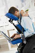 Businessman sitting on massage chair, getting back massage.?