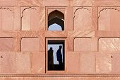 View at red outside wall of historical Badshahi Mosque with silhouettes, Lahore, Pakistan