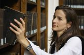 Young attractive woman standing at bookshelf in old library pulling out a book.
